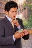 Fördärvad ung affärsman som accepterar några pengar från en skurk royaltyfri bild