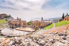 Fördärvar av den grekiska teatern av Taormina och den pittoreska bergskedjan från vulcanoen Etna till Castelmola royaltyfri foto