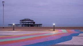 Fördärvar av den västra pir, Brighton, East Sussex, UK I förgrunden, Pebblet Beach och trottoaren som målas i regnbågeband arkivbild