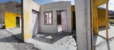 Fördärvar av det gamla huset, väggarna av guling, och vit, tomma öppningar av fönster och dörrar, där är inget främre vägg och ta Arkivfoton