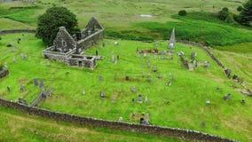Fördärvar av en gammal kyrka och kyrkogård i Skottland - flyg- surrlängd i fot räknat stock video