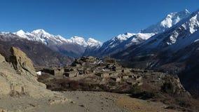 Fördärvar av en härlig gammal by nära Manang och höga berg av det Annapurna området royaltyfria foton