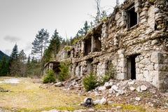 Fördärvar av gammal byggnad i skogen som omges med träd Arkivfoto