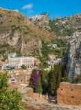 Fördärvar av gammalgrekiskateatern i Taormina med den Castelmola byn i bakgrunden Landskap av Messina, Sicilien, Italien royaltyfri fotografi