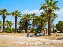 Fördärvar av kolonnerna för den forntida templet, palmträden och den blåa himlen Arkivbild