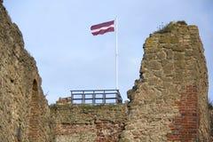 Fördärvar av Livoniabeställningsslotten byggdes i mitt av det 15th århundradet Bauska Lettland i höst Lettisk flagga på till Royaltyfria Foton