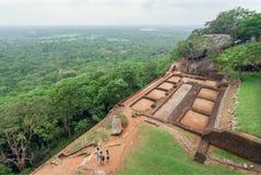 Fördärvar av slott för forntida stad på Sigiriya vaggar och några turister som går runt om arkeologiskt område Arkivfoto