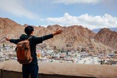 Fördelande armar för lycklig ung handelsresande i stadsbakgrund i Leh, Ladakh, Indien Royaltyfri Bild