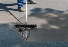 Fördelande asfalttätningsmedel på körbanan Royaltyfria Bilder