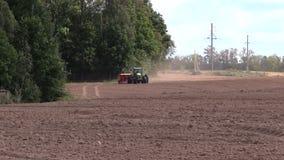 Fördelande gödningsmedel för traktor på kultiverat fält i höst arkivfilmer