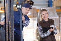 Fördelande gods för arbetare och för chef i lager Arkivfoto