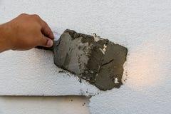 Fördelande mortel för arbetare över polystyrenet med spateln royaltyfria foton