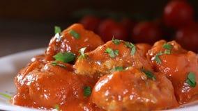 Fördelande ny huggen av persilja över köttbullar med tomatsås stock video