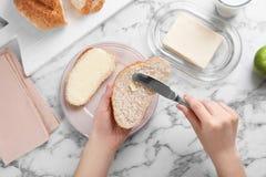 Fördelande smör för kvinna på skiva av bröd över tabellen royaltyfria bilder