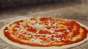 Fördelande tomatsås för kock på pizzadeg arkivfilmer