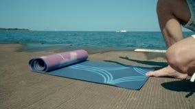 F?rdelande yoga f?r grabb som ?r matt vid havet Ung man som f?rbereder sig f?r meditation vid havet stock video