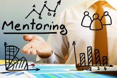 Förderungs-Konzept Mentor am Tisch im Büro lizenzfreie stockbilder