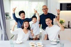 Fördjupad asiatisk familj av tre utvecklingar som har en måltogethe arkivfoto