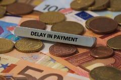 Fördröjning i betalning - ordet skrivevs ut på en metallstång metallstången förlades på flera sedlar Arkivfoto