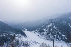 Fördunkla över bergen med en bosättning och en tät skog Arkivfoto