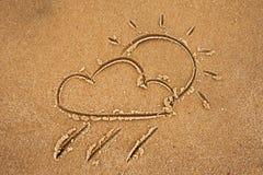 Fördunkla med regn och solen som dras på den sandiga stranden Arkivfoto