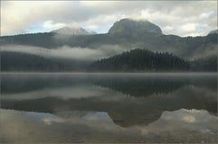 Fördunklar bergsjön i dimman för gryning royaltyfria foton