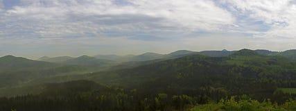 Fördunklar bred panorama Luzicke för hory berg, horisontsikten från kullestrednivrch, den gröna skogen och blå himmel, vit bakgru Arkivbild