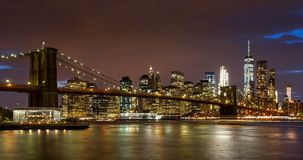 Fördunklar den finansiella områdesskyskrapor för Lower Manhattan, Brooklyn bron och East River med bortgång på skymning Manhattan lager videofilmer