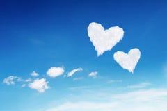 fördunklar formad vit hjärta för par på blå himmel Royaltyfri Bild