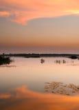 Fördunklar reflexion i vatten på solnedgången Royaltyfria Foton