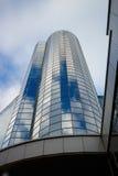 Fördunklar reflexion på glass byggnad för highrisen mot himmel Arkivbild