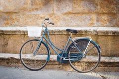 Förege cykeln mot en väggmonument Arkivfoto