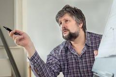 Föreläsare lärare, professor som förklarar ämnet sax och blyertspennor på bakgrunden av kraft papper Diskussion av akuta problem, royaltyfri fotografi