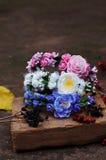 Förena från blommor, krans med kulöra blommor Handgjord blommakrans på utomhus- metallställning _ Konstgjorda blommor, mummel Arkivfoton