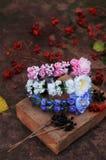Förena från blommor, krans med kulöra blommor Handgjord blommakrans på utomhus- metallställning _ Konstgjorda blommor, mummel Royaltyfria Foton