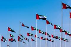 Förenade Arabemiraten flaggor som spolar i vinden mot blå himmel royaltyfri fotografi