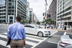 Förenta staterna: Affärsmananseende på den röda trafikljuset som korsar gatan Arkivbild