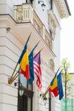 Förenta staterna för europeisk union och rumänska flaggor på en byggnadsfa royaltyfria foton