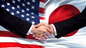 Förenta staterna- och Japan handskakning, internationellt kamratskap, flaggabakgrund arkivfoto