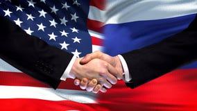 Förenta staterna- och Ryssland handskakning, internationellt kamratskap, flaggabakgrund fotografering för bildbyråer