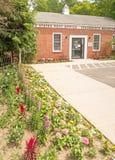 Förenta staterna postar - den kontorsbyggnadingången och trottoaren med blommaträdgården royaltyfri bild
