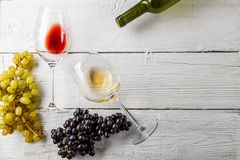 Föreställa överst av vinexponeringsglas, svärta och göra grön druvor, flaska på den vita trätabellen, tomt utrymme för text Arkivbild