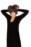 Föreställa av en härlig kvinna i svart klänning som poserar över vitba Arkivbilder