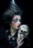 Föreställa en härlig fantasikvinna med skallen stor ljus rollbesättning som kantjusterar den kusliga fördjupade rengöringsduken  Arkivfoto
