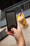 Föreställa fruktlunchasken på kontoret genom att använda den smarta telefonen Arkivbilder