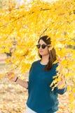Föreställd ung tonårs- flicka under ett träd med ett gult blad i höst Arkivbilder
