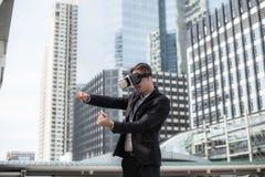 Föreställer den bärande virtuell verklighethörlurar med mikrofon VR för den Caucasian affärsmannen och för att köra en bil royaltyfria bilder