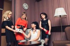 Företag av fyra flickor med handgjorda örhängen och stack påsar arkivbilder