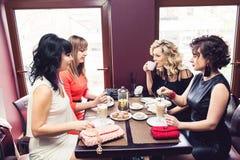 Företag av fyra stilfulla flickor på tabellen i kafé Flickor med handgjorda påsar och örhänge-borstar royaltyfri bild