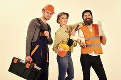 Företag av gladlynta arbetare, byggmästare, reparatör, stuckatör Man och kvinna med att le framsidor i hjälm och boilersuit arkivbild